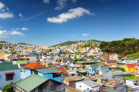 overlook: Beautiful colorful houses of Da Lat city (Dalat) on the blue sky background in Vietnam. Da Lat and the surrounding area is a popular tourist destination of Asia. Stock Photo