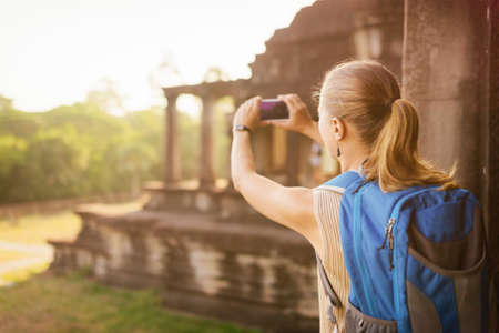 entries: Young female tourist with blue backpack and smartphone taking picture of the corner entries of the outside structure of the ancient mysterious temple complex Angkor Wat. Siem Reap, Cambodia.