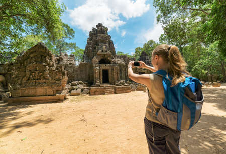 angkor wat: Young female tourist with blue backpack and smartphone taking a picture near the entrance to the ancient Preah Khan temple in Angkor. Siem Reap, Cambodia. Stock Photo
