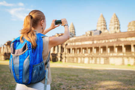 reap: Young female tourist with smartphone taking picture of the eastern facade of the ancient temple complex Angkor Wat. Towers of the temple and blue sky in background. Siem Reap, Cambodia. Stock Photo
