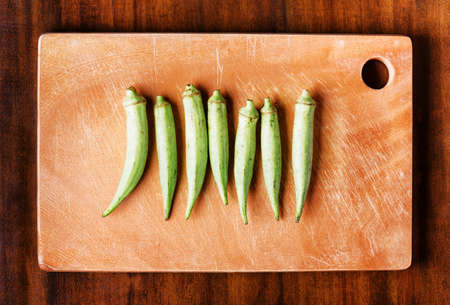 folate: Top view of fresh green seed pods okra on a wooden board on a table. Healthy eco food rich in vitamins, folate, antioxidants, calcium and potassium. Popular product of organic farming in Asia.