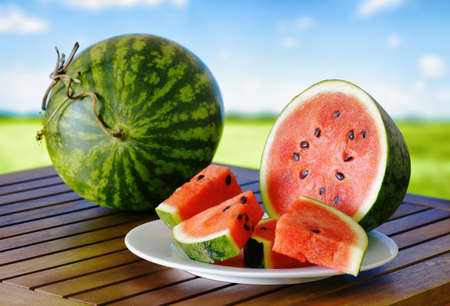 Fresh ripe red watermelons and slices on a wooden table. A green field and a blue sky in the background. A healthy eco sweet food rich in vitamins. Popular product of organic farming. photo