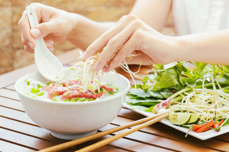 vietnamese food: Young woman sprinkles sprouts to the Pho Bo in street cafe of Vietnam. The Pho Bo is a traditional Vietnamese beef noodle soup with garnish of leaves of cilantro and Asian basil. Popular street food.