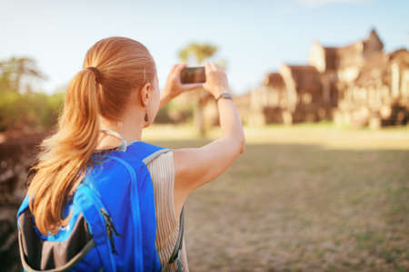 take a history: Closeup view of young female tourist with smartphone taking picture of facade of the ancient temple complex Angkor Wat in morning sun on blue sky background. Siem Reap, Cambodia.