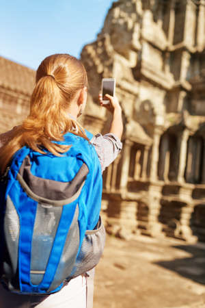take a history: Young female tourist with blue backpack and smartphone taking picture of upper gallery at ancient temple complex Angkor Wat in morning sun. Siem Reap, Cambodia.
