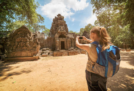 take a history: Young female tourist with blue backpack and smartphone taking a picture near the entrance to the ancient Preah Khan temple in Angkor. Siem Reap, Cambodia. Toned image.