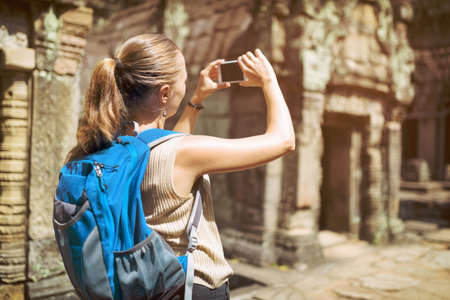take a history: Closeup view of young female tourist with blue backpack and smartphone taking picture of ruins in the ancient Preah Khan temple in Angkor. Siem Reap, Cambodia. Toned image.