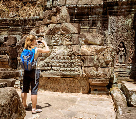take a history: Young female tourist with blue backpack and smartphone taking picture of the bas-reliefs among mysterious ruins of ancient Preah Khan temple in Angkor. Siem Reap, Cambodia.