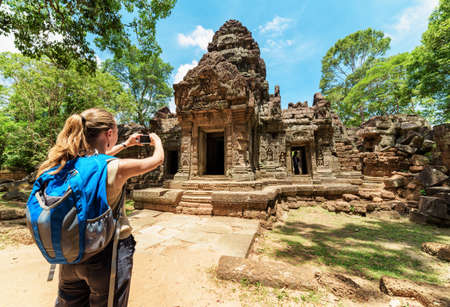 siem reap: Young female tourist with smartphone taking picture of the gopura under blue sky near the entrance to ancient Preah Khan temple in Angkor. Siem Reap, Cambodia.