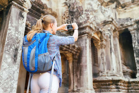 take a history: Young female tourist with blue backpack and smartphone taking picture among mysterious ruins of ancient temple complex Angkor Wat. Siem Reap, Cambodia. Stock Photo