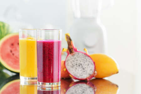 liquidiser: Fresh fruit smoothies on kitchen table. Blender is visible in background. Yellow mango juice and red pitaya juice on fruits background. Healthy eco food rich in vitamins.