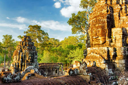 bayon: Giant stone face of ancient Bayon temple in Angkor Thom in evening sun. Siem Reap, Cambodia. Mysterious ruins, woods and blue sky with clouds in background. Angkor Thom is a popular tourist attraction
