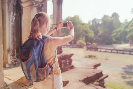 take a history: Young female tourist with blue backpack and smartphone taking picture among mysterious ruins of ancient temple complex Angkor Wat in Siem Reap, Cambodia. Toned image.