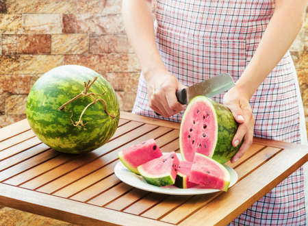 slicing: Young woman in apron slicing fresh ripe juicy red watermelon on a wooden table. Healthy eco sweet food rich in vitamins. Popular product of organic farming. Stock Photo