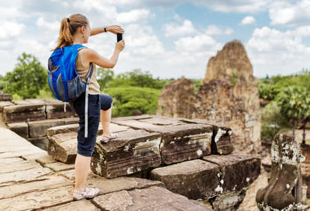 take a history: Young female tourist with backpack taking picture with smartphone of the gopura from the top of ancient Pre Rup temple in Angkor on blue sky background. Siem Reap, Cambodia.