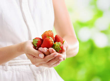 handful: Handful of fresh ripe red juicy strawberries in hands of young woman in white dress on nature background. Healthy eco sweet food rich in vitamins. Popular product of organic farming. Stock Photo