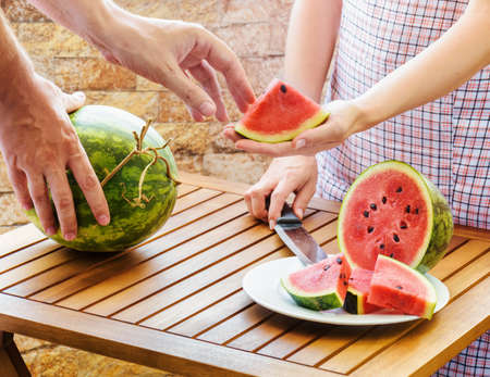 slicing: Young woman in apron giving to young man a slice of fresh ripe juicy red watermelon. Watermelons on a wooden table. Healthy eco sweet food rich in vitamins. Popular product of organic farming. Stock Photo