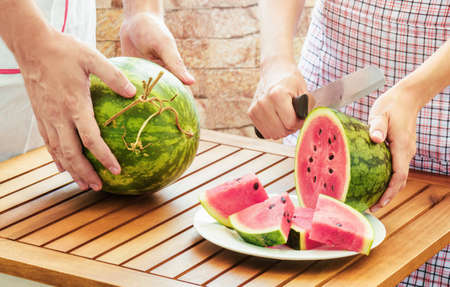 sliced watermelon: Young woman in apron slicing ripe watermelon on wooden table. Young man putting watermelon on table. Healthy eco food rich in vitamins. Product of organic farming. Stock Photo