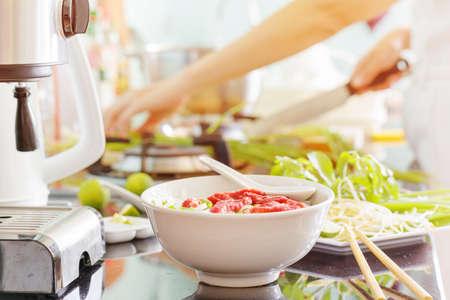 ベトナム牛肉麺フォー ボー台所のテーブルにコリアンダー、アジア バジルと豆もやしの葉の飾りです。若い女性は、バック グラウンドで料理です 写真素材