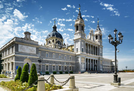 saint: Side view of the Cathedral of Saint Mary the Royal of La Almudena on the blue sky background with white clouds in Madrid, Spain. Madrid is a popular tourist destination of Europe. Stock Photo