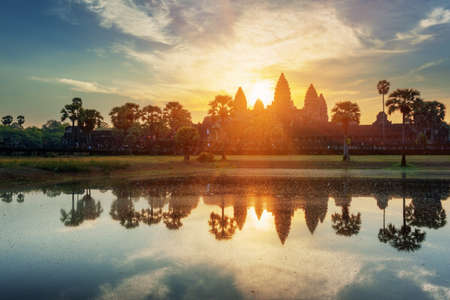 Mysterious towers of ancient temple complex Angkor Wat at sunrise. Siem Reap, Cambodia. Temple Mountain and the sun reflected in lake at dawn. Angkor Wat is a popular tourist attraction.