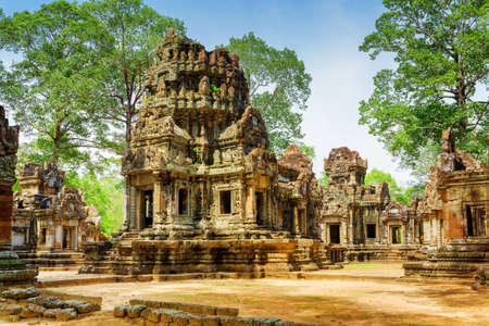 Ancient buildings of Thommanon temple in enigmatic Angkor, Siem Reap, Cambodia. Mysterious Thommanon nestled among rainforest. Blue sky in background. Amazing Angkor is a popular tourist attraction. Stock Photo