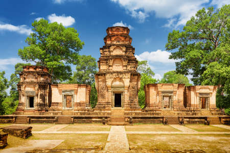 temple tower: Prasat Kravan temple is Khmer monument in ancient temple complex Angkor Wat on sunny day in Siem Reap, Cambodia. Woods and blue sky in background. Angkor Wat is a popular tourist attraction. Stock Photo