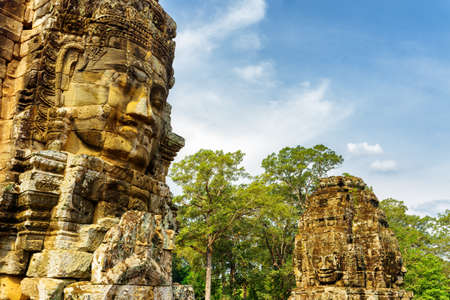 hindu temple: Enigmatic giant stone faces of ancient Bayon temple in Angkor Thom, Siem Reap, Cambodia. Mysterious Angkor Thom nestled among rainforest. Amazing Angkor Thom is a popular tourist attraction. Stock Photo
