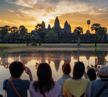 siem reap: Asian tourists taking picture of ancient temple Angkor Wat at sunrise. Siem Reap, Cambodia. Towers of mysterious Angkor Wat reflected in lake at dawn. Angkor Wat is a popular tourist attraction. Stock Photo