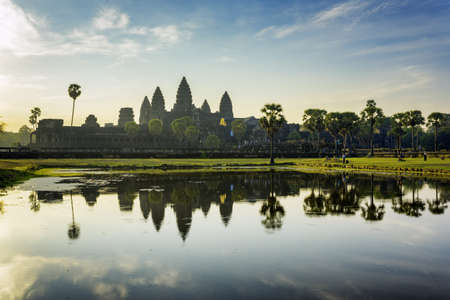 Towers of ancient temple complex Angkor Wat at sunrise. Siem Reap, Cambodia. Temple Mountain reflected in lake at dawn. Angkor Wat is a popular tourist attraction and iconic Khmer monument.