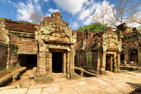 siem reap: Ancient buildings of enigmatic Preah Khan temple in amazing Angkor on blue sky background. Siem Reap, Cambodia. Mysterious Angkor is a popular tourist attraction.