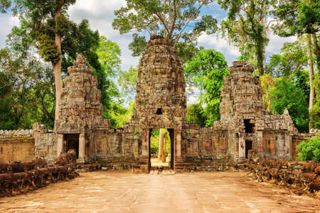 gateway: Gateway to ancient Preah Khan temple in Angkor, Siem Reap, Cambodia. Gopura on woods background. Enigmatic Angkor is a popular tourist attraction. Stock Photo