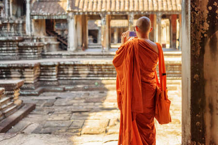 Buddhist monk with smartphone taking picture of courtyard in ancient temple complex Angkor Wat, Siem Reap, Cambodia. Amazing Angkor Wat is a popular destination of tourists and pilgrims. Stock Photo