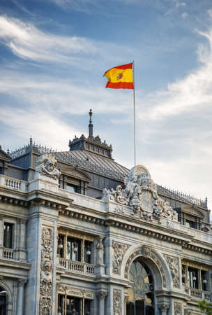madrid  spain: The flag of Spain fluttering on building of the Bank of Spain (Banco de Espana) in Madrid, Spain. Madrid is a popular tourist destination of Europe.