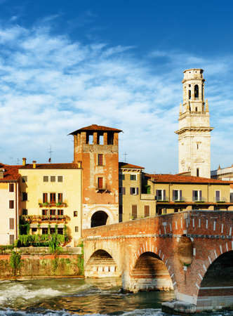 pons: View of the Ponte Pietra (Pons Marmoreus) and white bell tower of the Verona Cathedral in Italy. Verona is a popular tourist destination of Europe. Stock Photo