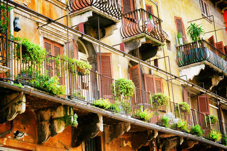 destination scenic: Scenic balconies of old house decorated with flowers in pots, Verona, Italy. Verona is a popular tourist destination of Europe.