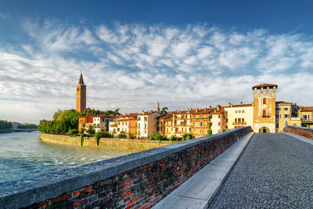 Beautiful view of waterfront of the Adige River from the Ponte Pietra (Pons Marmoreus) in Verona, Italy. Colorful facades of old houses and bell tower of Santa Anastasia church in morning sun. Stock Photo - 43321322