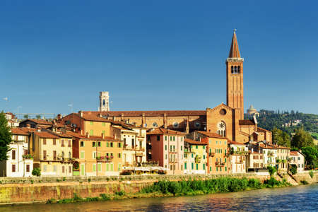 old houses: Beautiful view of colorful facades of old houses on waterfront of the Adige River in Verona, Italy. The Santa Anastasia church on blue sky background. Verona is a popular tourist destination of Europe