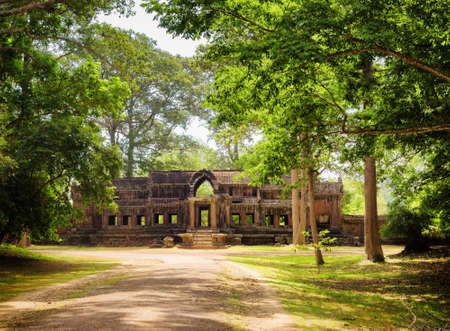 east gate: Road through rainforest runs beside mysterious ruins of Ta Kou Entrance (East Gate) in ancient temple complex Angkor Wat in Siem Reap, Cambodia. Landscape in jungle.