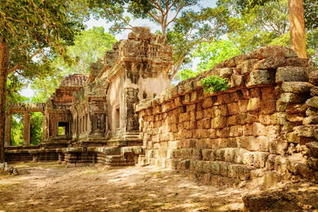 khmer: Side view of Ta Kou Entrance (East Gate) in ancient temple complex Angkor Wat in Siem Reap, Cambodia. Woods in background. Angkor Wat is a popular tourist attraction. Stock Photo