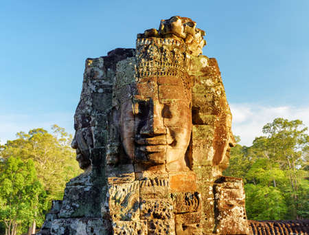temple tower: Enigmatic face-tower of ancient Bayon temple in evening sun. Mysterious Bayon temple nestled among rainforest in Angkor Thom, Siem Reap, Cambodia. Amazing Angkor Thom is a popular tourist attraction. Stock Photo