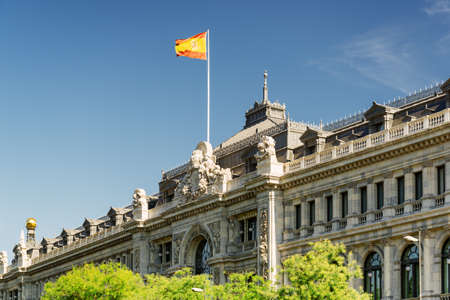 The flag of Spain fluttering on building of the Bank of Spain (Banco de Espana) in Madrid, Spain. Blue sky in background. Madrid is a popular tourist destination of Europe.