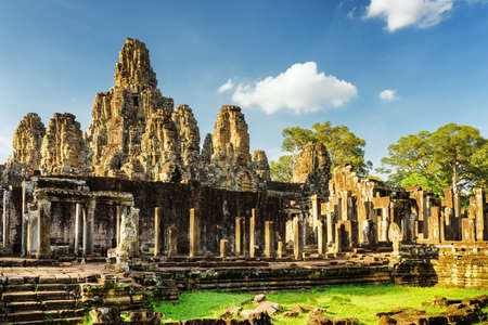 siem reap: Mysterious ruins with stone faces of ancient Bayon temple in Angkor Thom in evening sun. Siem Reap, Cambodia. Blue sky with clouds and woods in background. Angkor Thom is a popular tourist attraction.