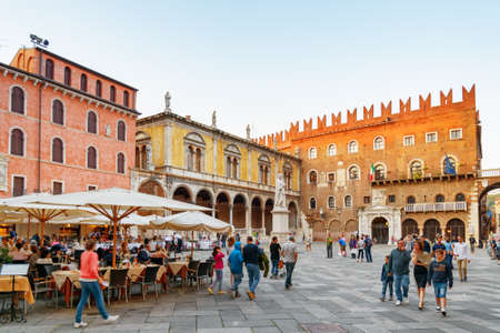 VERONA, ITALY - AUGUST 24, 2014: Street cafes on Piazza delle Erbe (Market square) in Verona, Italy. Verona is a popular tourist destination of Europe. Publikacyjne