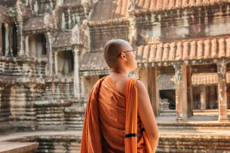 SIEM REAP, CAMBODIA - MAY 4, 2015: Closeup view of Buddhist monk looking at courtyard of ancient temple complex Angkor Wat. Amazing Angkor Wat is a popular destination of tourists and pilgrims.
