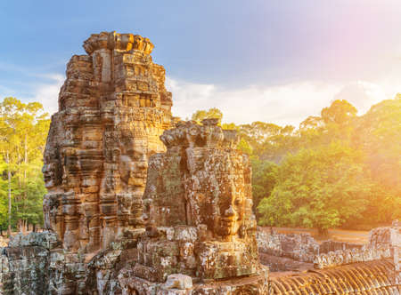 Enigmatic face-towers of ancient Bayon temple in evening sun. Mysterious Bayon temple nestled among rainforest in Angkor Thom, Siem Reap, Cambodia. Amazing Angkor Thom is a popular tourist attraction. Editorial