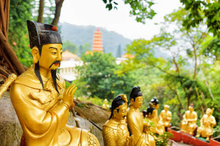 monastery: Golden Buddha statues along the stairs leading to the Ten Thousand Buddhas Monastery on background of a red pagoda and forest in Hong Kong. Hong Kong is popular tourist destination of Asia. Stock Photo