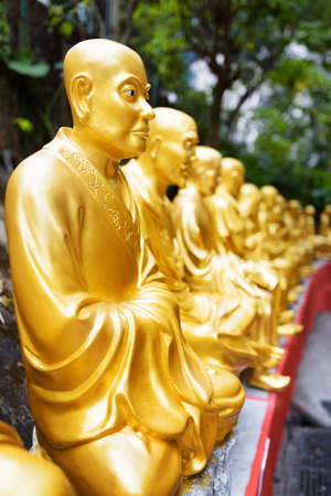 buddha face: Golden Buddha statues along the stairs leading to the Ten Thousand Buddhas Monastery on nature background in Hong Kong. Hong Kong is popular tourist destination of Asia. Stock Photo