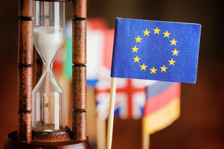 politics: Political concept with flag of the European Union (EU). Time is running out. Closeup view of hourglass and flag of the European Union (EU). Flags of European countries in background. Stock Photo