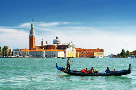 venice canal: View of the Venetian Lagoon with gondola and the Church of San Giorgio Maggiore on island of the same name in Venice, Italy. Venice is a popular tourist destination of Europe. Editorial